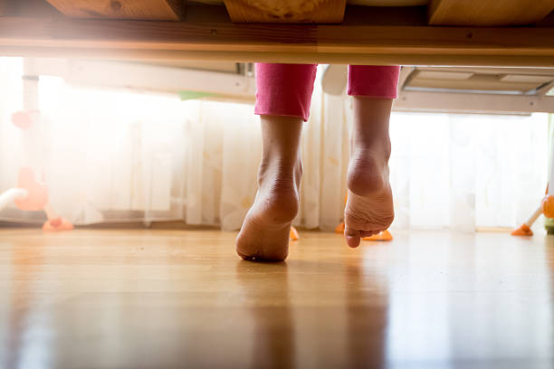 Image from under the bed on girl stepping on floor View from under the bed on girl stepping on wooden floor at bedroom sole of foot stock pictures, royalty-free photos & images