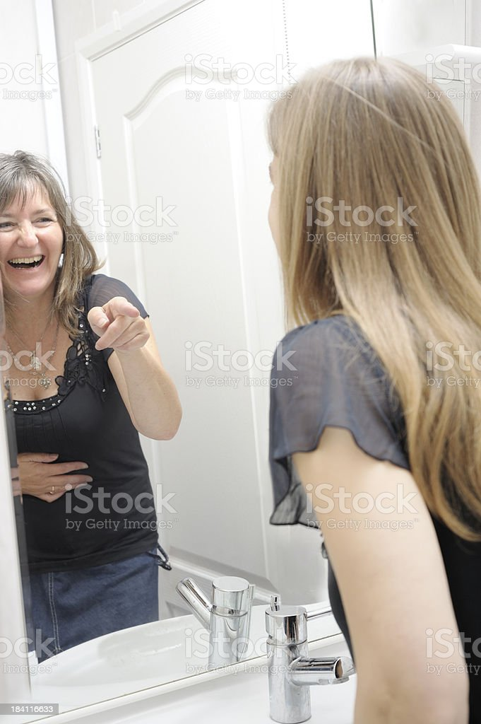 Image in mirror mocking woman stock photo