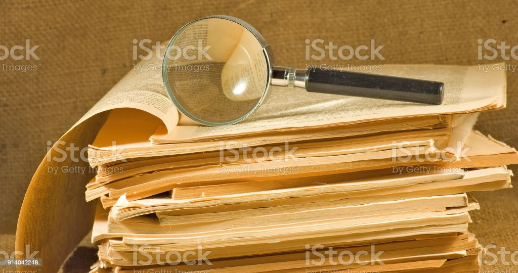 image notebooks, magazines, glasses and magnifying glass on a table close-up stock photo