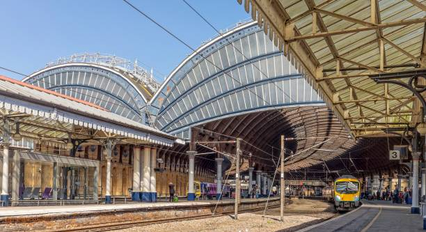 Image of a 19th Century intricately designed railway canopy curving above the platform.  A train waits to depart. Classic view of a railway station.  A train is at the platform waiting to depart.  Overhead are ornate 19th Centrury canopies. depart stock pictures, royalty-free photos & images