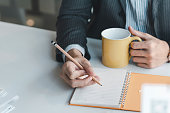 Image of a businessman holding a pencil and a coffee cup the documents is blank place the office.