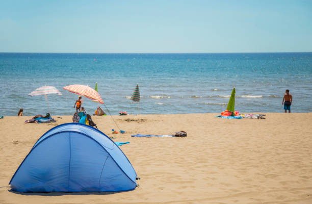 image of a camping tent on the almost deserted beach and the sea in the background stock photo