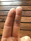 istock Image of a caucasian man's index and middle fingers with happy smiley faces drawn in blue biro, emojis smileys drawn on finger pads showing fingerprint skin pattern 1200371473
