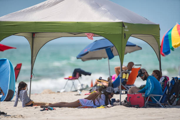 image of a family under a tent on the beach memorial day weekend - memorial day weekend стоковые фото и изображения