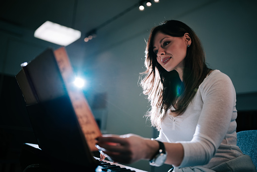 Image of a female pianist turning the sheet music while playing.