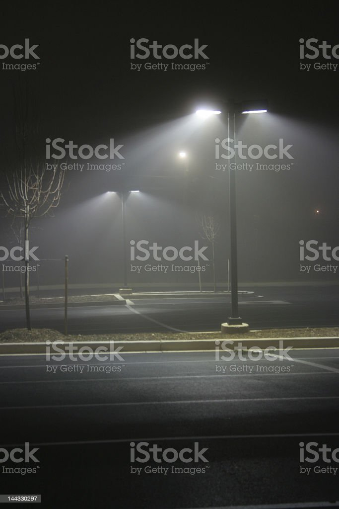 Image of a foggy parking lot at night stock photo