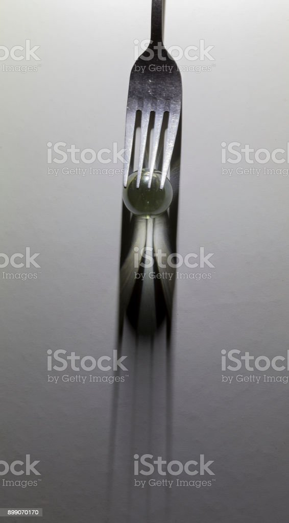 Image of a fork and small glass ball to make a shadow from spotlight stock photo