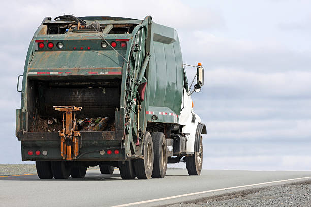 Image of a garbage truck driving down a road  stock photo