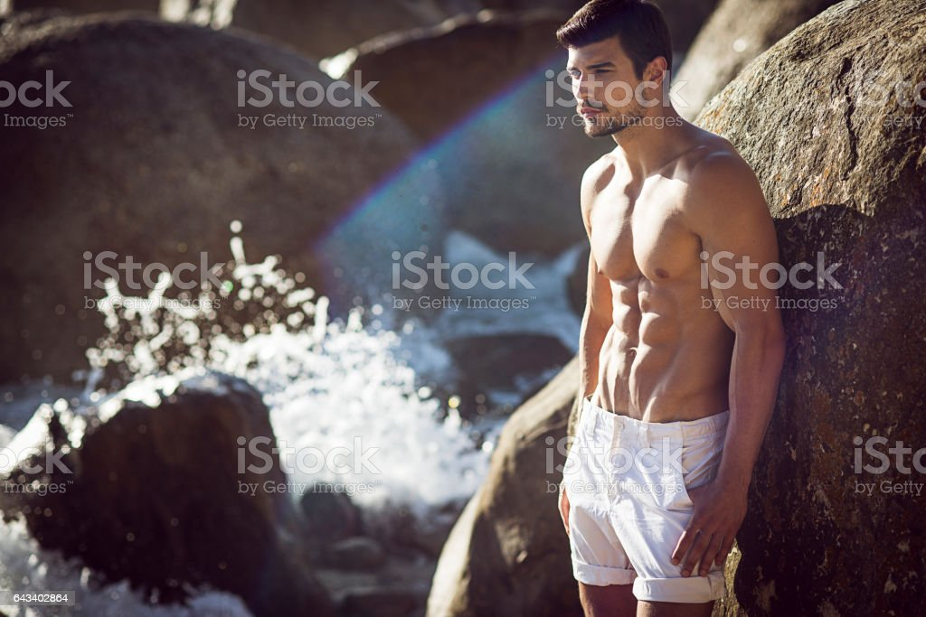 image of a handsome fit man at sea stock photo