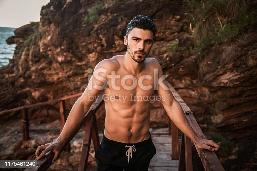 519676858 istock photo Image of a handsome fit man posing near sea 1175461240