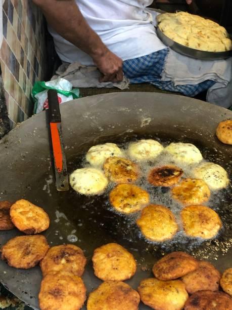 Bild eines Mannes, der Aloo tikki/Aloo tikki Chaat macht und auf einer großen Pfanne in heißem Öl, indischen Straßenfutter, indischen Street Food Stall, ungesunde Ernährung, Neu Delhi, Indien, Delhi Bauch frittiert wird – Foto
