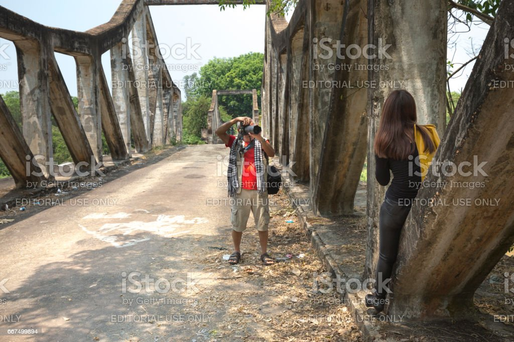 Image of a photographer taking photos a model at a destroyed bridge in the past war foto stock royalty-free