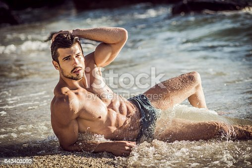 519676858 istock photo image of a ripped man lying down on the sand 643403092