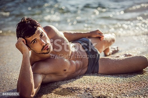 519676858 istock photo image of a ripped man lying down on the sand 643403324