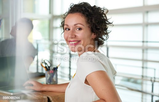 istock Image of a succesful casual business woman using laptop during 598065244
