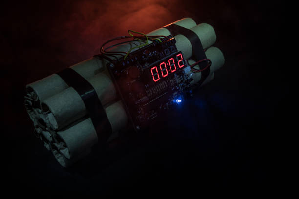 Image of a time bomb against dark background. Timer counting down to detonation illuminated in a shaft light shining through the darkness – zdjęcie