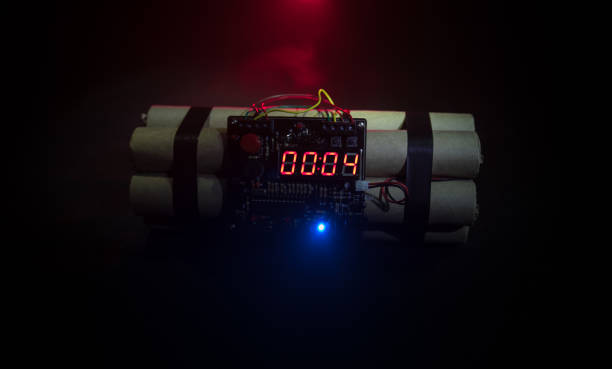Image of a time bomb against dark background. Timer counting down to detonation illuminated in a shaft light shining through the darkness Image of a time bomb against dark background. Timer counting down to detonation illuminated in a shaft light shining through the darkness, conceptual image explosive stock pictures, royalty-free photos & images