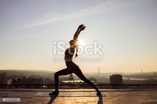 istock image of a woman doing yoga on a rooftop 622212170