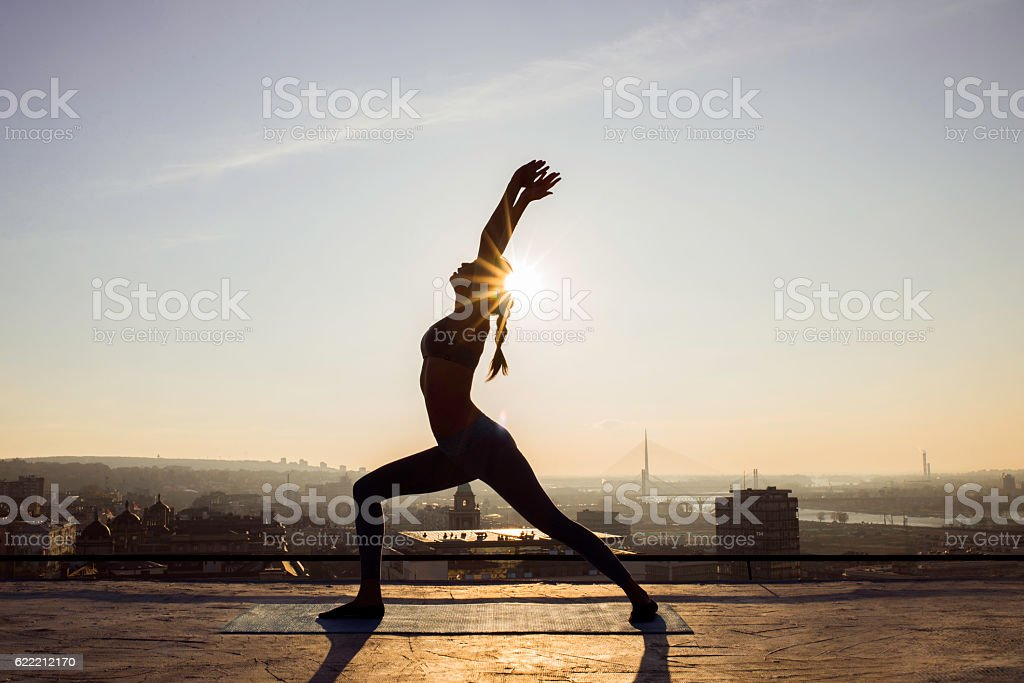 image of a woman doing yoga on a rooftop stock photo