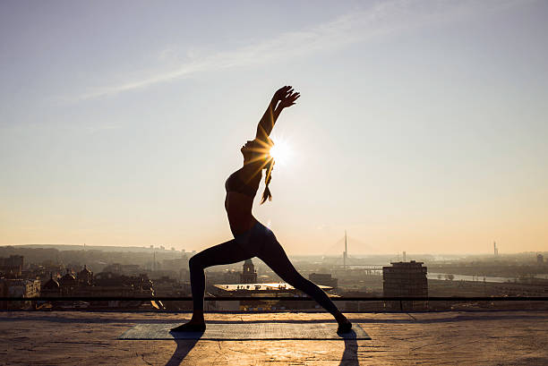image of a woman doing yoga on a rooftop - foto de stock