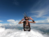 Image of a woman parachutist in casual clothing smiling and having fun in free fall.