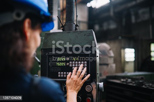 Image of a woman working as a technical manual operator in the STEM sector. She is working in a heavy industry production facility.