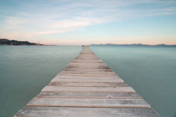 Image of a wooden pier to the sea, with silky water on the island of Mallorca stock photo