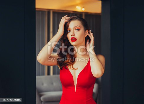 172214590istockphoto image of a young business woman at a formal evening meeting. bright lipstick and scarlet dress, attractive pretty girl with red and copper hair and blue gray eyes looking directly at the camera 1077567984