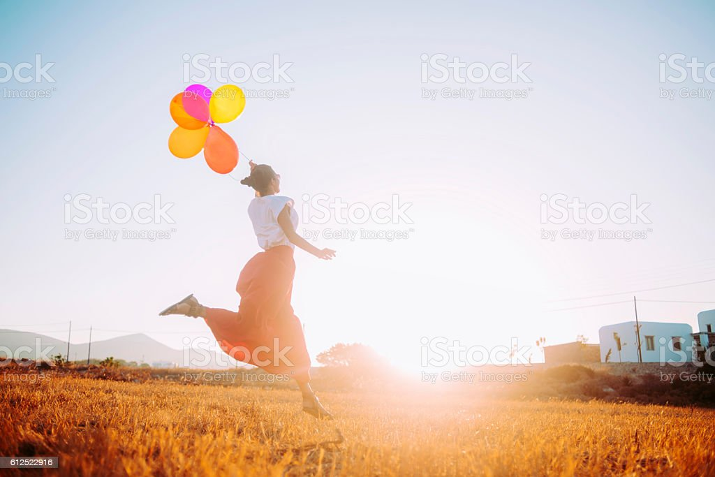 image of a young woman running in the field stock photo