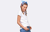 istock Image of adorable cheerful young blonde woman wearing white t-shirt, blue headband with hands in the pockets, smiling and looking to the camera, isolated over white studio background 1168987863