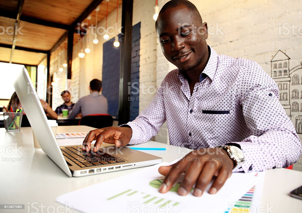 Image of african american businessman working on his laptop stock photo
