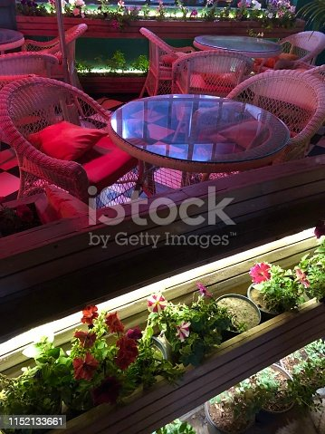 Stock photo of al fresco dining terrace at night with wicker patio chairs and round glass dining tables, patio garden furniture with spotlights, wooden garden decking flower troughs of petunias photo, garden lighting