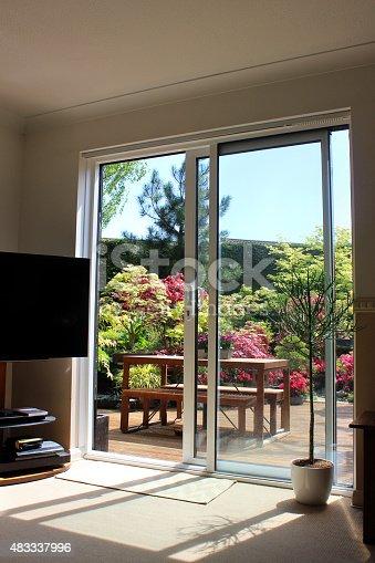 istock Image of aluminium patio doors overlooking back garden with decking 483337996