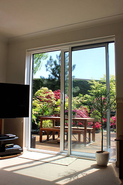 image of aluminium patio doors overlooking back garden with decking - sliding stock photos and pictures