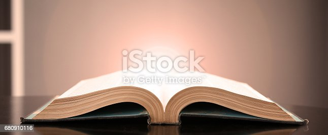 istock Image of an open book with a beautiful yellow light on a black background. 680910116