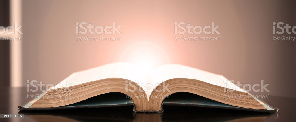 Image of an open book with a beautiful yellow light on a black background. stock photo