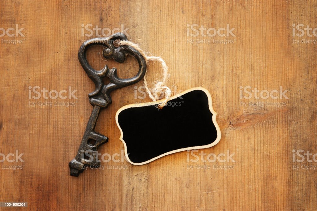 Image of antique key and empty blackboard tag over old wooden table