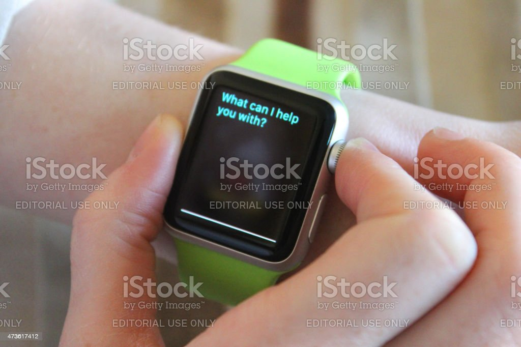 Image of Apple Watch being used, Siri app clock face stock photo