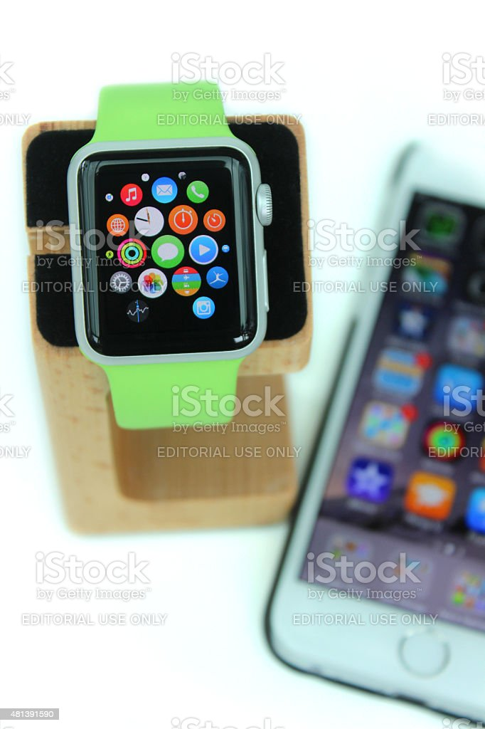 Image of Apple Watch on stand paired with iPhone 6 stock photo