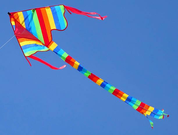 Image of arrowhead kite flying in sky with rainbow stripes stock photo