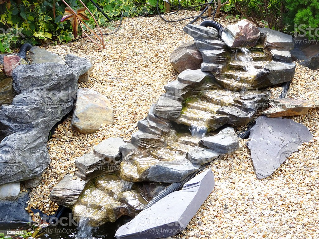 Image of artificial waterfalls with plastic slate rocks, flowing water stock photo