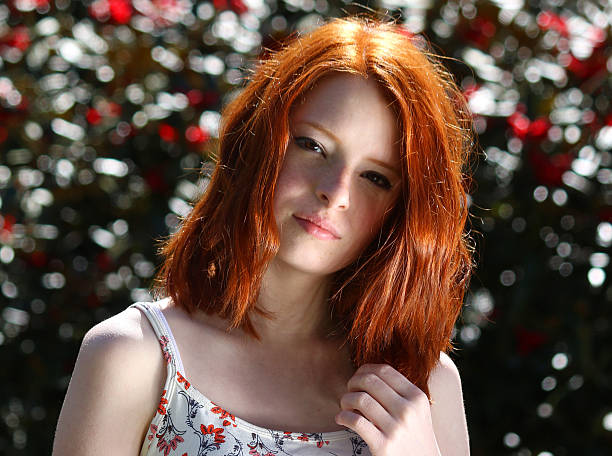 image of attractive red-haired girl portrait wearing suntop, azalea background - tween models stock photos and pictures