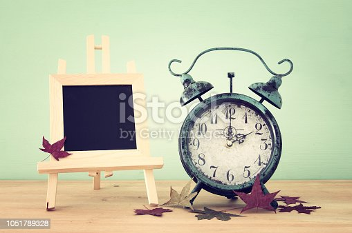 istock Image of autumn Time Change. Fall back concept. Dry leaves and vintage alarm Clock on rustic wooden table. 1051789328