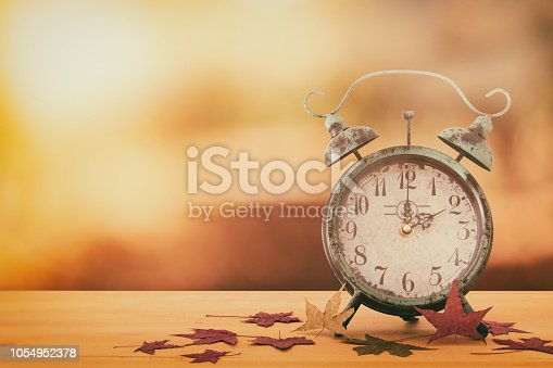 istock Image of autumn Time Change. Fall back concept. Dry leaves and vintage alarm Clock on rustic wooden table. 1054952378