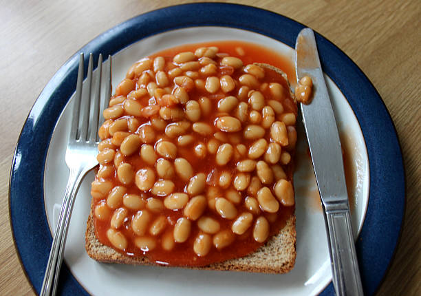 Image of baked beans on toast (wholemeal bread), with cutlery stock photo
