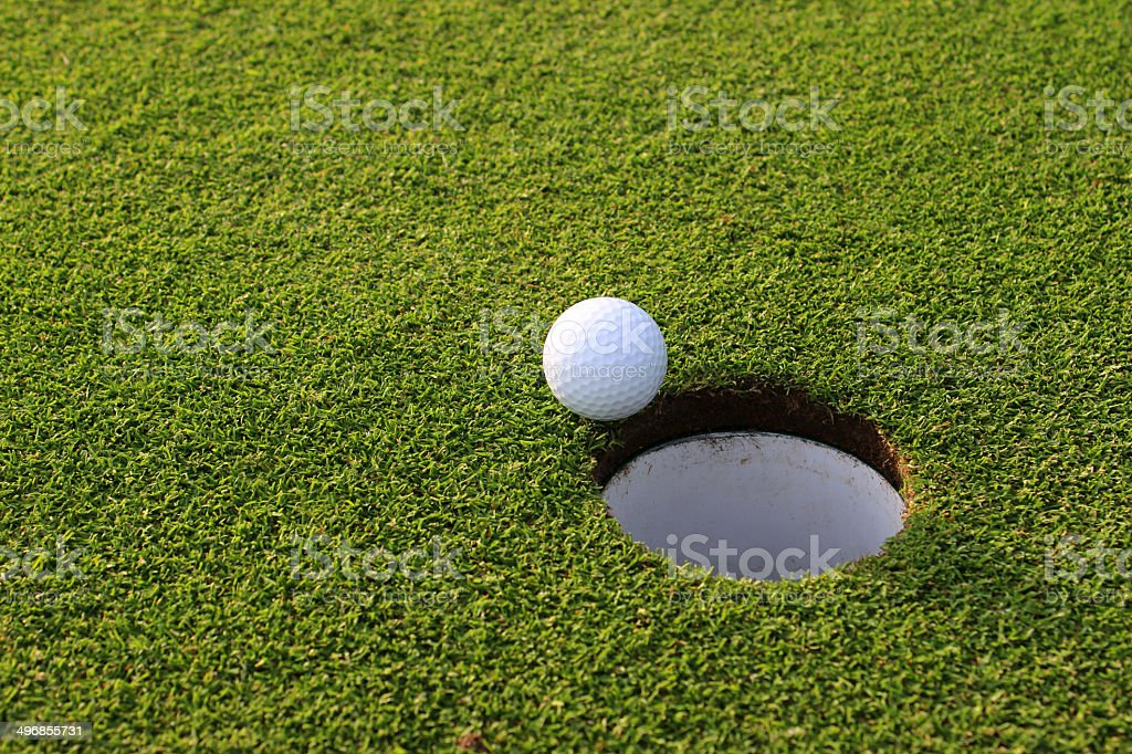 Photo showing a ball in the sunshine, right next to the hole on a...