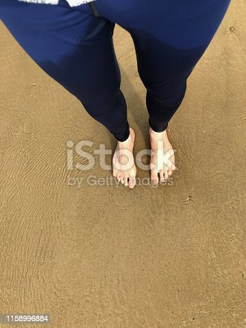 174919648 istock photo Image of barefoot man with two white feet and toes standing on wet beach wearing tight blue men's leggings pants / sportswear jogging trousers getting wet, paddling in sea waves on golden beach, barefoot feet sink in wet sinking sand causing footprints 1158996884