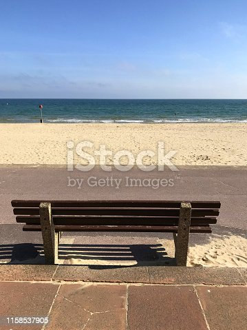 Stock photo of beachfront bench overlooking calm sea, sunny blue sky and golden sand of Bournemouth Beach / Poole Sandbanks, Dorset, England, UK, stone concrete and wooden bench seat for tourists on English seaside holiday vacation to sit down and enjoy the view