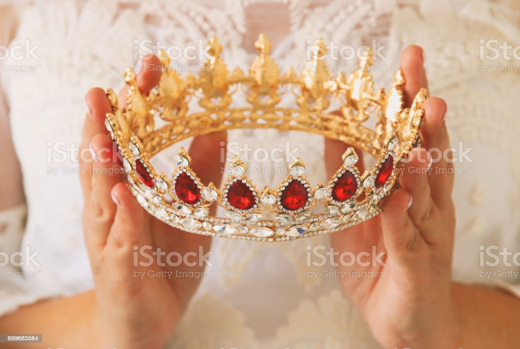 image of beautiful lady with white lace dress holding diamond crown. fantasy medieval period. stock photo