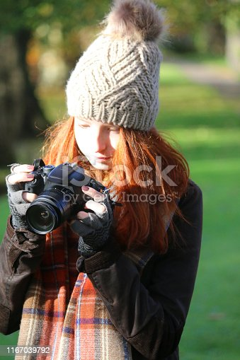 Stock photo of beautiful teenage girl with red ginger hair in autumnal garden wearing scarf and hat, looking through camera view finder.
